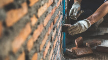 Man Bricklayer Installing Bricks On Construction Site