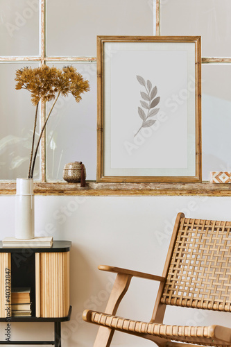 Photo Modern composition of living room interior with design armchair, wooden shelf, old window, dried flowers in vase, brown mock up poster frame, decoration and elegant personal accessories