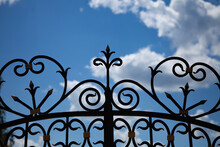 Great Photo. Summer Time. Sunlight. Photo From Bottom To Top. Forging Against The Blue Sky And White Clouds. Fragment Of A Forged Fence Close-up.