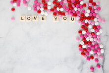 The Words Love You Written In Scrabble Tiles On A Marble Kitchen Counter Top Surrounded By Valentines Candy