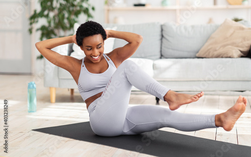 Fototapeta Young black woman exercising in her house gym, doing abs exercises, working out