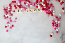 The Words In Love  Written In Scrabble Tiles On A Marble Kitchen Counter Top Surrounded By Valentines Candy