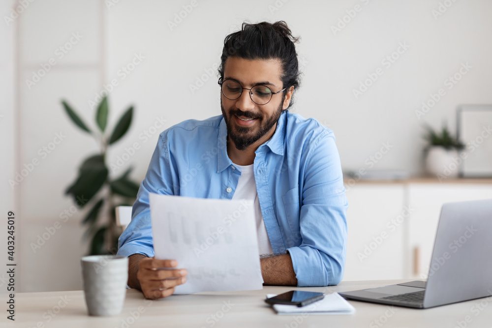 Fototapeta Young Arab Male Self-Entrepreneur Working With Papers At Desk In Home Office