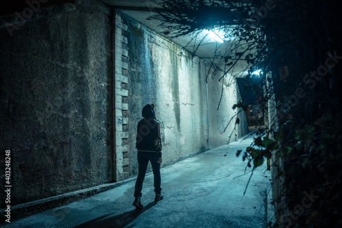 Fotografering Lonely woman walking in a dramatic mystic dark alley at night