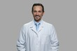 Happy male pharmacist looking at camera on gray background. Portrait of smiling engineer in lab coat.