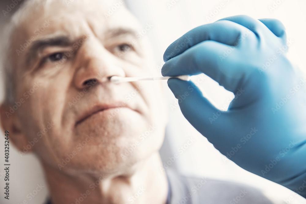 Fototapeta Medical worker wearing protective equipment testing senior old man for dangerous corona virus using test swab stick