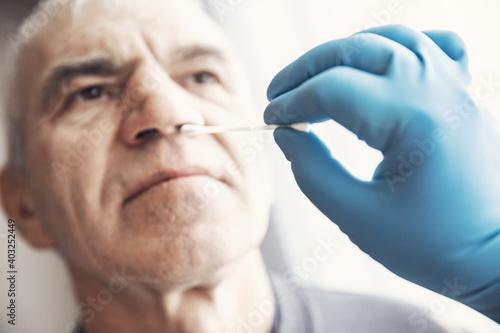 Obraz Medical worker wearing protective equipment testing senior old man for dangerous corona virus using test swab stick - fototapety do salonu