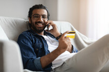 Handsome Arabic Man Holding Credit Card And Talking On Cellphone At Home