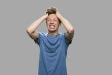 Desperate Teenage Boy On Gray Background. Stressed Furious Teen Boy Shouting And Pulling His Hair. Nervous Breakdown Concept. Human Negative Expressions.