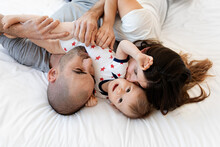 Mother And Father Kissing Cute Baby On Bed