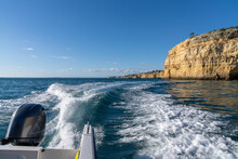 Outboard Motor Of A Speeding Coast With Ocean And Rocky Coast Behind