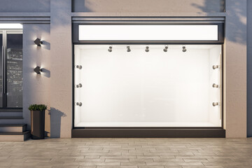Luxury boutique with blank glass storefront and backlight lamps.