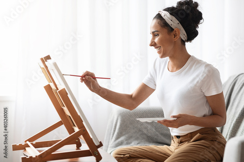 Fototapeta Inspired brunette woman sitting on couch and painting