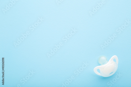 Fényképezés White silicone baby soother on light blue table background