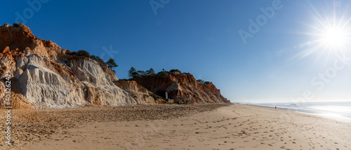 Fotografia, Obraz panorama view of a wide empty golden sand beach with colorful sand cliffs on a s
