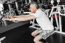 Photo Of A Man With Gray Hair Performing An Exercise Squatting In The Gym