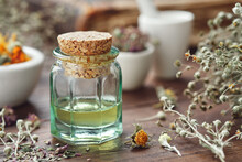 Essential Oil Bottle, Mortars Of Dry Medicinal Herbs And Old Book On Background.