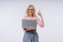 Smart Elderly Caucasian Woman With Laptop Pointing At Copy Space Isolated Over Grey Background