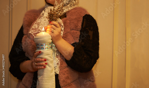 Female hands holding bouquet of flowers with candle in the church at baptism Fototapeta