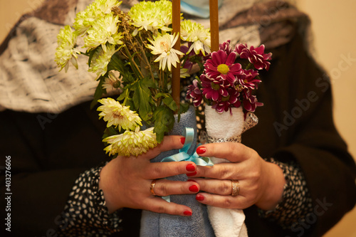 Fényképezés Female hands holding bouquet of flowers with candle in the church at baptism