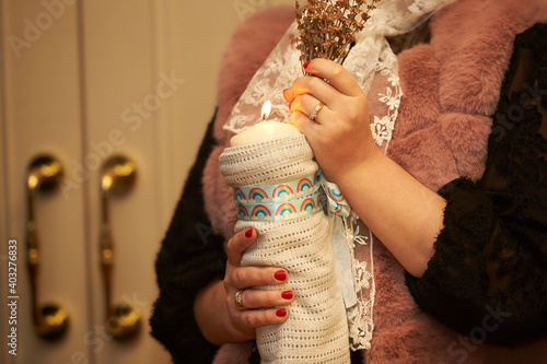 Fotografija Female hands holding bouquet of flowers with candle in the church at baptism