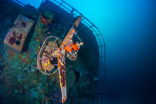 A Large, Upturned Shipwreck On The Sea Floor Near A Tropical Coral Reef