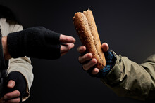 Close-up Photo Of Homeless People's Hands Sharing Food, One Bum Give Bread To Other One