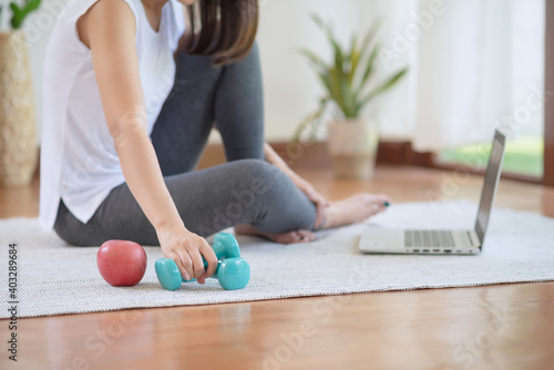 Fototapeta Asian woman staying fit by exercising at home for healthy trend lifestyle obraz