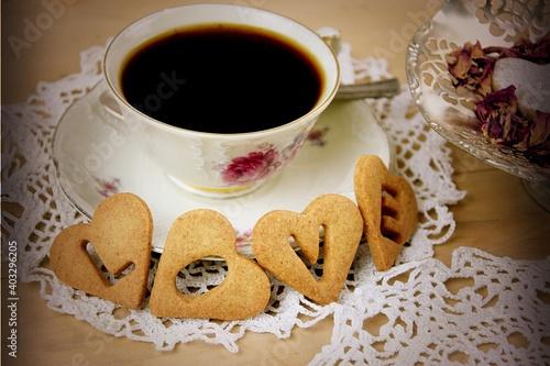 LOVE ciasteczka serduszka z napisem na drewnianym tle, filiżanka z kawą, płatki róż,Walentynkowe powitanie, vintage
