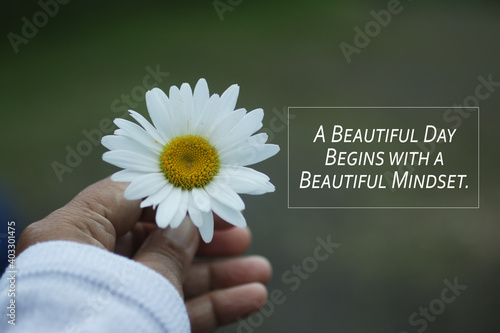 Obraz Inspirational quote - A beautiful day begins with a beautiful mindset. Motivational words concept with hand holding a white daisy. Happiness and success concepts. - fototapety do salonu