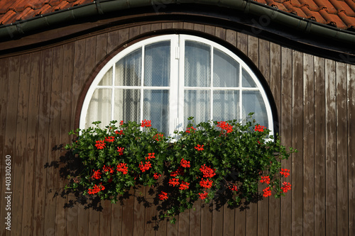 Foto Historic building with semi rounded window and flowers