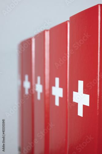 Fotografia, Obraz Red office folders with a white cross - swiss flag imitation