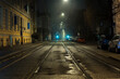 Old Norwegian central street with tram paths lit by soft night lights.