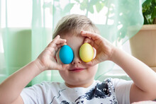 Portrait Of A Cute Child With Easter Eggs. Easter Lunch. The Feast Of Holy Easter.