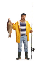 Full Length Portrait Of A Fisherman Holding A Fishing Rod And A Carp Fish