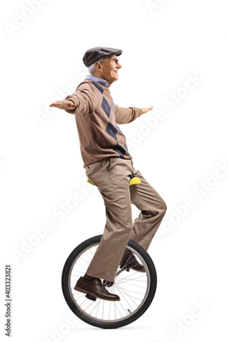 Fototapeta Full length profile shot of an elderly man riding a mono-cycle and spreading arms obraz