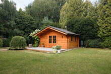 Orange Wooden Hut In The Garden With Many Tall Trees. Garden Shed With Lawn In Front Of Him