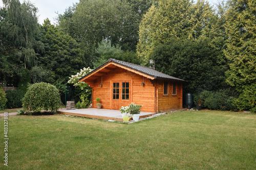 Cuadros en Lienzo Orange wooden hut in the garden with many tall trees