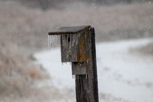 Ice Icicles Covered Bird House On Fence Post In November