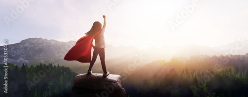 Obraz little girl dreaming of being a superhero in a beautiful mountain landscape with a raised fist - fototapety do salonu