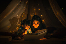 Mom And Daughter Read Bedtime Stories Fairytale Together Before Going To Bed