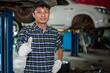 Asian auto mechanic works car repairs at his own repair shop.