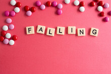 The Words Falling Written As A Flat Lay In Wood Scrabble Tiles On A Plain Red Background Surrounded By Red, White, And Pink Candies