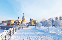 Siberia. Irkutsk. View From The Snow-covered Lower Embankment Of The Angara River To The Epiphany Cathedral And The Monument To The Founders Of The City On A Cold Day. Beautiful Winter Cityscape