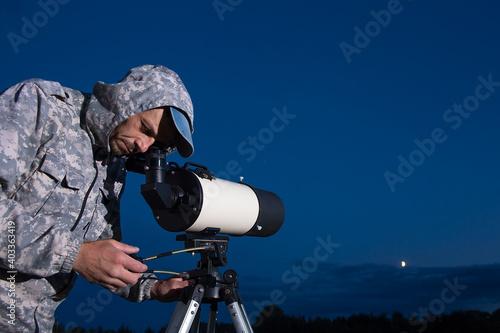The man looks through a telescope Fotobehang