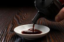 醤油を小皿に注ぎ入れる