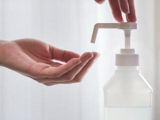 アルコール消毒スプレーで手を消毒する様子。新型コロナウイルス・COVID-19対策。