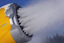 Snow Cannon During Operation. Snow Gun Spraying Artificial Ice Crystals To Ski Piste, Snowmaking In Winter Sports Resort, Trees In Background.