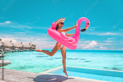 Obraz Happy fun luxury hotel vacation woman jumping of joy taking selfie with pink inflatable swimming pool mattress at overwater bungalow resort. - fototapety do salonu