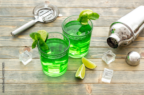Obraz Margarita green cocktail with bar tools, lime and mint - fototapety do salonu